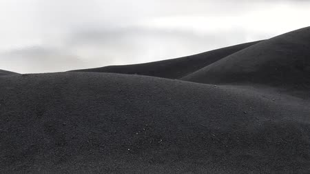 crest dune : The black cold desert winter. Dunes of black sand under the gloomy sky. Inhospitable environment Stock Footage