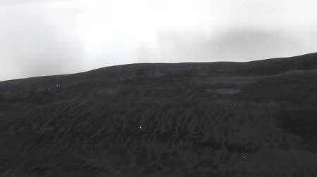desolado : The black cold desert winter. Dunes of black sand under the gloomy sky, rare event of sparse snowfall in the desert. Below - a temporary body of water like an oasis. Inhospitable environment