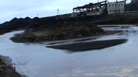 grit : Mine for the extraction of minerals. Pumping of dirty groundwater (flooding) and foamy polluted river Stock Footage
