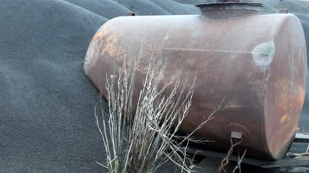 dene : The black desert in death valley. Metal water barrel covered with black sand, drought and dry weeds