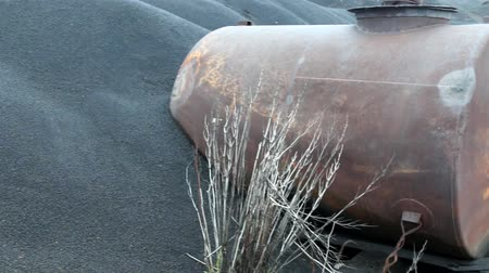 flange : The black desert in death valley. Metal water barrel covered with black sand, drought and dry weeds