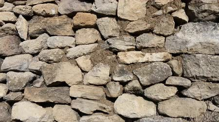 enclosure : The stone fence is made of crude stone (limestone) on loam mortar. The millennial ancient methods of construction, history of the building Stock Footage