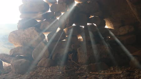 dojem : The entrance to the cave is stoned. Suns rays pierce in the gaps between the stones and burn like spotlights