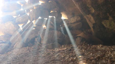 stoned : The entrance to the cave is stoned. Suns rays pierce in the gaps between the stones and burn like spotlights