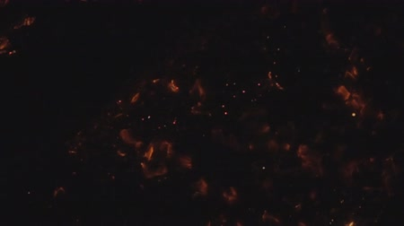 into the camera : Embers of the extinguished fire and flying ashes. Super slow motion 1000 fps