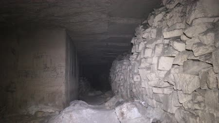 бункер : Old underground passage, dungeon, catacombs lined with stones and slabs with paths from speleologists (spelunking)