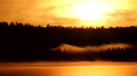 растворение : Spring late evening on a lake with fog, remains of ice and disturbing clouds. Foggy lake surrounded by forests
