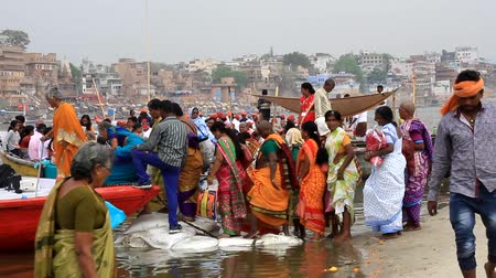 waters : India, Varanasi - March 20, 2018: Pilgrims sit in boat on shore of Ganges river at Holy city Varanasi. Worship of sacred waters of Ganges. Bright saffron clothes of pilgrims