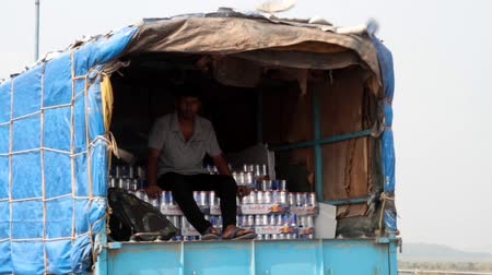 camionagem : India, Goa - 31 March 2018: Transportation of products by truck, food and drinks. Loader sitting in the back