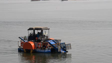 moloz : India, Varanasi - March 20, 2018: Wheeled steamer for collecting floating debris on the Ganges river Stok Video
