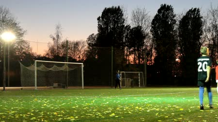 лучше : Russia, St. Petersburg-October 15, 2018: Night football. Teenagers training football competitions at soccer stadium with lighting, autumn sunset, the wind drives the fallen leaves. Youth football