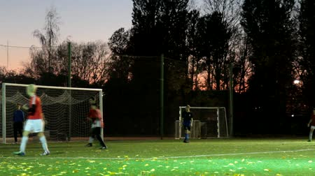Russia, St. Petersburg-October 15, 2018: Night football. Teenagers training football competitions at soccer stadium with lighting, autumn sunset, the wind drives the fallen leaves. Youth football