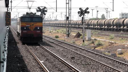tampon : India, new Delhi - March 26, 2018: locomotive runs parallel to passenger train. transport of India by rail Stok Video