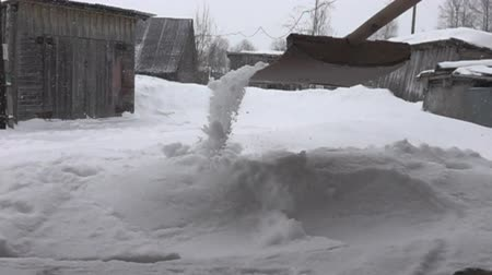 preocupações : Snowfall in the hamlet and snow removal with a wooden shovel, winter worries of countryman. Sheds were leaning under the weight of the fallen snow. Super slow motion 1000 fps. Stock Footage