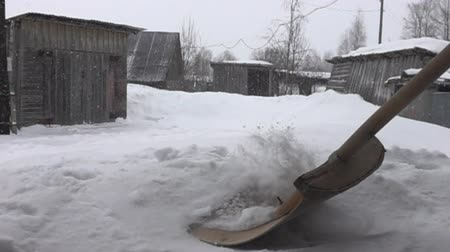 preocupações : Snowfall in the hamlet and snow removal with a wooden shovel, winter worries of countryman. Super slow motion 1000 fps.