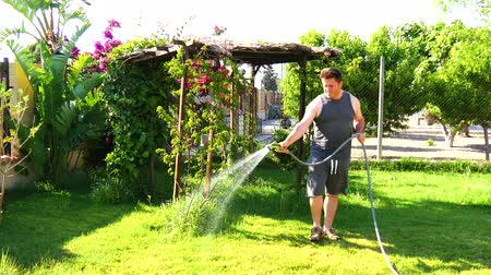 opieka : Man watering the garden with hose 4K
