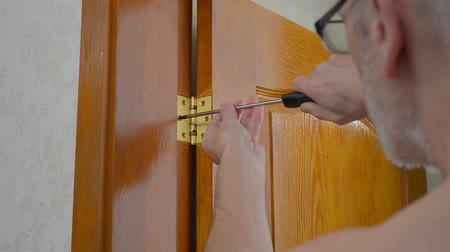 fitting : A man is using a screwdriver to screw a Door hinge