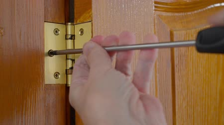 монтаж : A man is using a screwdriver to unscrew a Door hinge