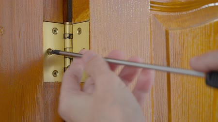 монтаж : A man is using a screwdriver to screw a Door hinge