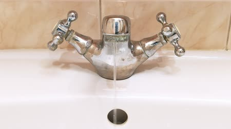 drinking water supply : Water flowing slowly from the bathroom tap during a period of scarcity. 4K video Stock Footage