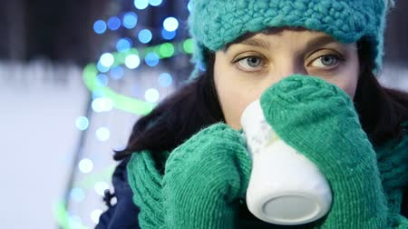 knitted gloves : HD Close up shot Christmas time a girl is chilling and drinking tea next to Christmas tree