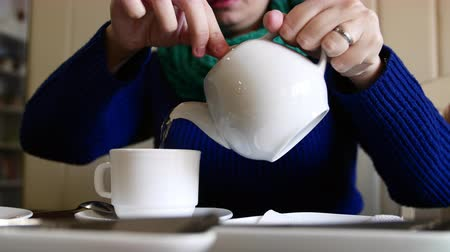 кувшин : 4k Close up shot a woman pouring tea into cup from teapot