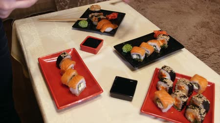 seafood dishes : Cook puts plates with sushi at the table.Serving sushi in the red plate