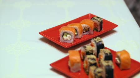 nori : Plates with sushi onto plate. Woman prepares food at table. Time to serve the dish