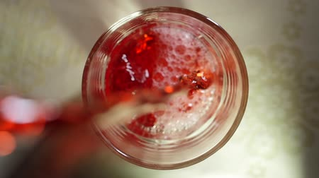 сверкающий : Top view filling cherry juice into a glass. Close up