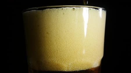 пивоваренный завод : Dark beer pouring into a cold glass on a black background. Close up. Slow motion