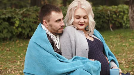 plodnost : HD Couple is sitting in a park husband is covering his pregnant wife with a blanket