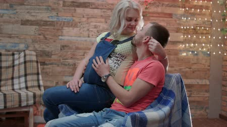 hlazení : HD Young couple is in studio, the man is sitting and his pregant wife is on his kness