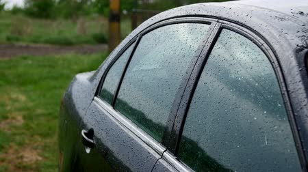 clear liquid : 4K The side view of the black car under the rain Stock Footage