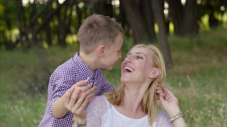 отпрыск : 4K Mother and son are in the park and son covers the eyes of the mother Стоковые видеозаписи