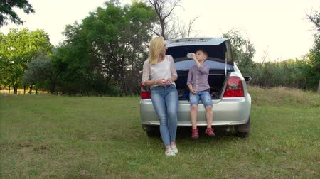 bordas : 4k Young woman and her son sit in the trunk of a car. Travel concept Stock Footage
