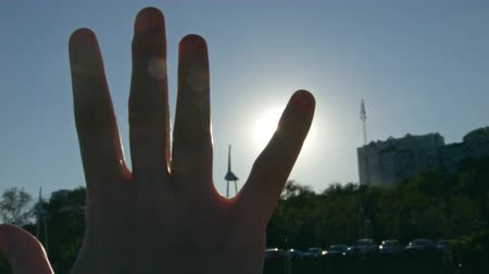 raised : 4K Close-up of raised hand in the sky against the sun in nature, spirituality, camera movement