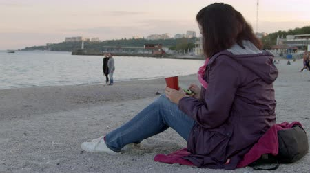 grãos de café : 4K the beautiful lady in spring coat sits on the beach with cup of hot drink and uses her phone