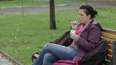 descuidado : 4K Woman is drinking coffee in the park on a bench.