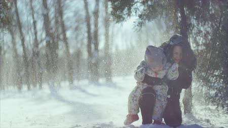klidný : 4K Winter games. Mother and child under the snowfall