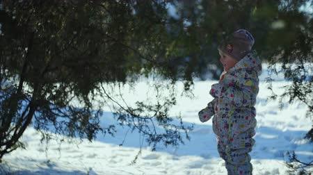 tédio : 4K The kid is standing in the park full of snow and after runs laughing Stock Footage