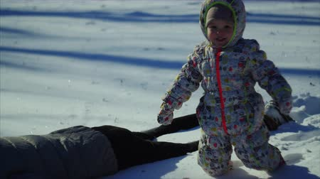 položit : 4K The child reaches the mother and lays down the snow as his father did