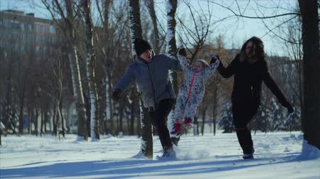snow angel : 4K Happy familly runs in the park. Mother and father hold the child and lift him up Stock Footage
