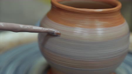 moldagem : 4k Close up shot of the brush painting the pot of raw clay