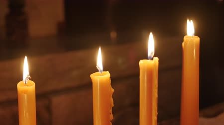 mumlar : Close up shot of wax candles burn on the church altar. The focus on the flame Stok Video