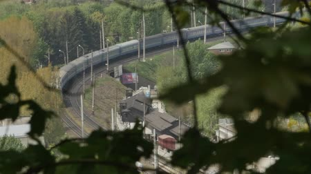se movendo para cima : Aerial view of train turning on tracks. The shot is made among the tree leaves