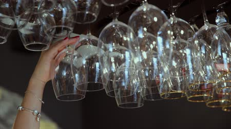 behind bars : Close up of empty glasses hanged up in a bar. The female hand takes one glass