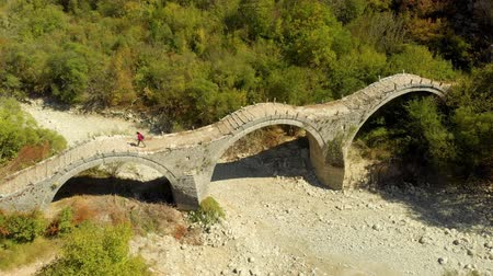 Aerial view of a tourist crossing Plakidas arched stone bridge of Zagori region Stok Video