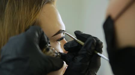 Eyebrow correction. Cosmetologist puts eyebrows with brush