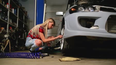 chave inglesa : sexy blonde in a garage repairs a car