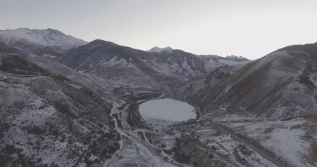 Top view of the frozen lake in the mountains. Drone Aerial Flight in the mountains in winter.